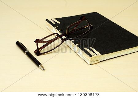 Glasses pen and black notebook on wooden background. group of glasses pen and black notebook in education concept.