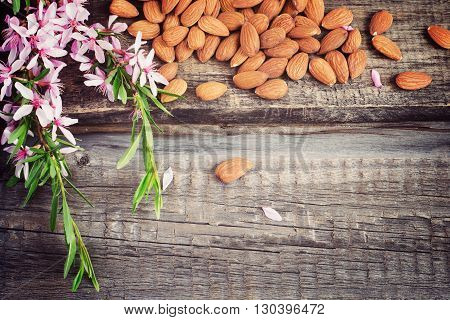 Old wooden background with crumbled almonds and flowers tinted. Top view with copy space
