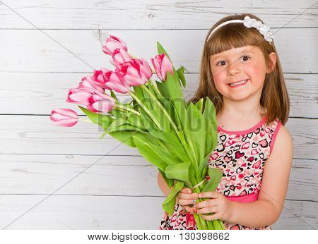 little irl with tulips in hands over white wooden background