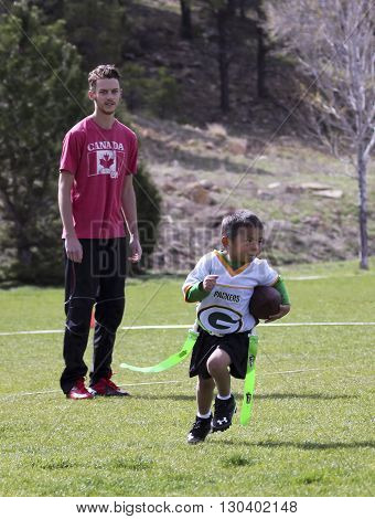 FLAGSTAFF, ARIZONA, MAY 14. Foxglenn Park on May 14, 2016, in Flagstaff, Arizona. A young man coaches a youth flag football player at Foxglenn Park in Flagstaff Arizona.