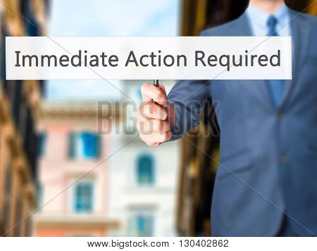 Immediate Action Required - Businessman Hand Holding Sign