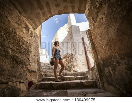 Girl is walking downstairs under a arc and between typical white buildings in a street of Ginosa a south italian village similar to Matera.