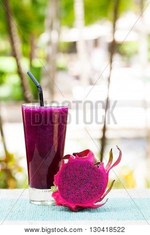 Glass of dragon fruit smoothie, juice and fresh pitahaya on a outdoor tropical background Copy space