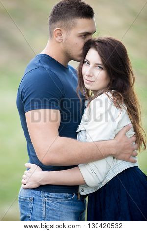 Cuddling Young Couple In Park