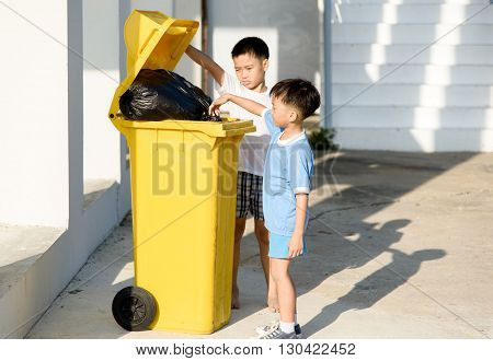 Young Asian boy carry garbage in plastic bag for eliminate in the yellow bin under the sunligh poster