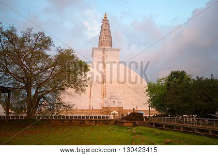 The ancient Dagoba Ruwanwelisaya in the rays of the setting sun. Anuradhapura, Sri Lanka