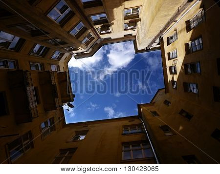 Cloudy sky seen from the closed quadrangle well courtyard in Lviv, Ukraine.