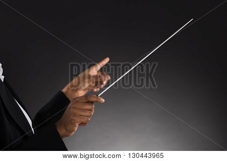Close-up Of Female Orchestra Conductor Holding Baton Over Black Background poster