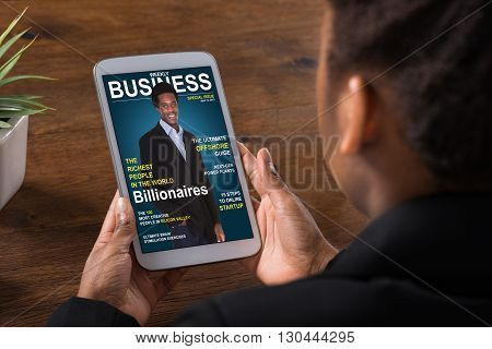 Close-up Of A Businesswoman Reading Online Magazine On Digital Tablet In Office