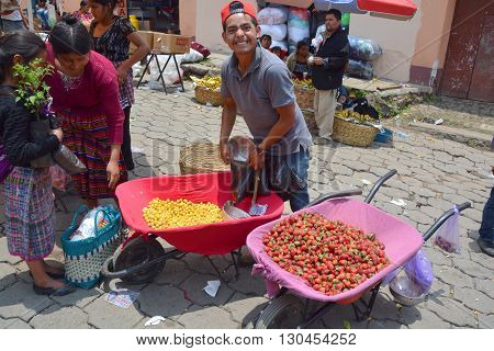 QUETZALTENANGO GUATEMALA APRIL 28 2016 : Youg man sells fruits in Quetzaltenango maket. This native market is the most colorful in Central America