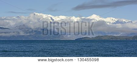 White Capped Peaks Appearing Behind the Morning Clouds in the Valdez Arm of Prince William Sound in Alaska