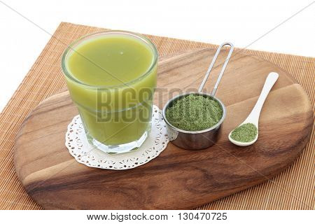 Wheat grass health drink with powder in scoop and spoon on a maple wood board over bamboo and white background. Also used by body builders, in weight training and to boost the immune system.