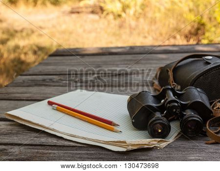 Binoculars notebook with a blank page on a wooden background