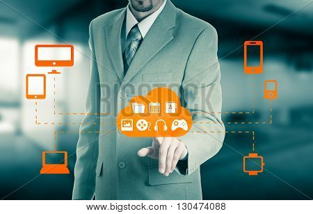 Businessman touching a cloud connected to many objects on a virtual screen concept about internet of things.