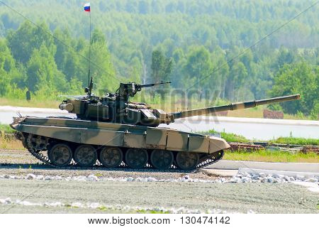 Nizhniy Tagil, Russia - July 12. 2008: Tank T-80s moving through cross-country terrain with obstacles. Display of fighting opportunities of arms and military equipment. RAE exhibition