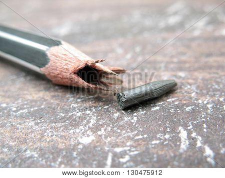 close up broken pencil, black pencil broken on old table