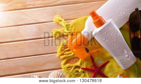 Two Spray Suncream Lying With Shells On Wooden Slats Top