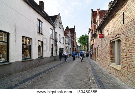 Bruges Belgium - May 11 2015: Tourists walking on street in Bruges Belgium. Bruges is the capital and largest city of the province of West Flanders in the Flemish Region of Belgium.