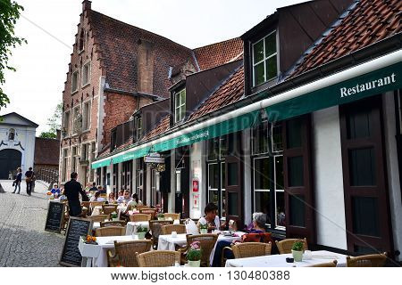 Bruges Belgium - May 11 2015: Tourist at outdoor cafeteria in Bruges Belgium. Bruges is the capital and largest city of the province of West Flanders in the Flemish Region of Belgium.
