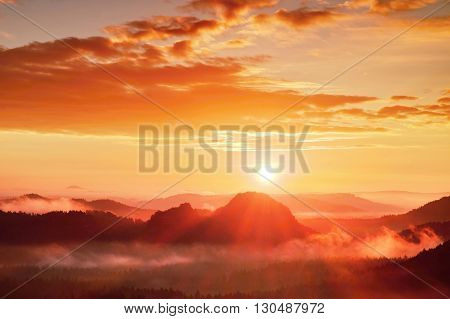 Red Misty Daybreak. Foggy Autumn Morning In A Beautiful Hills. Peaks Of Hills Are Sticking Out From