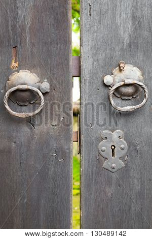 Two old iron ring handles and lock on an old weathered wooden door standing ajar showing a glimpse of a garden
