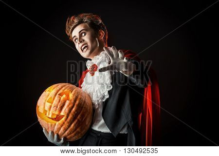 Portrait of a handsome vampire with pumpkin. Halloween. Dracula costume.