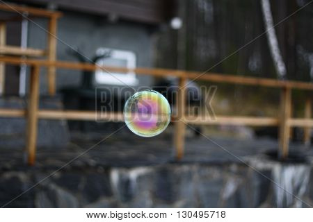 Rainbow bubble on gray background house from northern forests