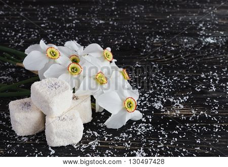Traditional turkish dessert rahat lokum with coconut and narcissus on black wooden background poster