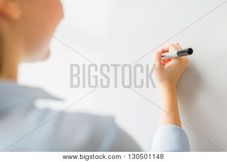 office, business, people and education concept - close up of woman with marker writing or drawing something on white board or wall