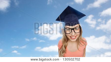 people, graduation and education concept - smiling young student woman in mortarboard and eyeglasses over blue sky and clouds background