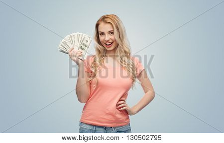 money, finances, investment, saving and people concept - happy young woman with dollar cash money over gray background