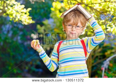 Funny little kid boy with glasses, books, apple and backpack on his first day to school or nursery. Child outdoors on warm sunny day, Back to school concept