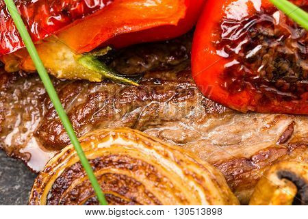 Mexican beef steak with grilled onions and red paprika on grill metal pan. Decorated with fresh herbs. Macro. Photo can be used as a whole background.