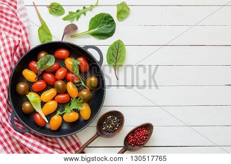 Multi colored cherry tomatoes in pan, spices, kitchen textile and fresh green salad leaves on white wooden backdrop. Top view, flat lay food. Copy space for text