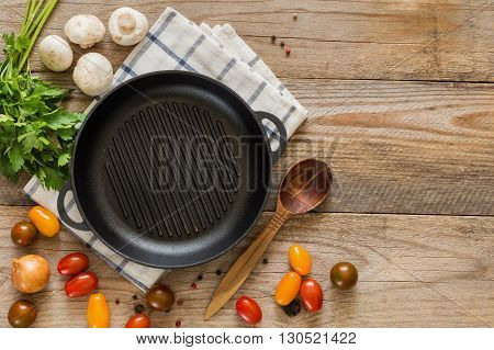 Cooking ingredients for a healthy and vegan life: cherry tomatoes, onion, mushrooms, spices and greens on rustic wooden backdrop. Empty skillet in middle. Top view, copy space for text