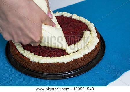 Creamy vanilla frosting being swirled onto sponge cake with professional pastry tip