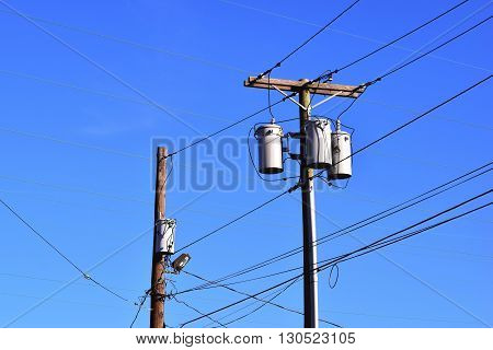 Electric utility poles with  transformers against blue sky background.
