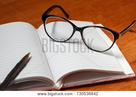 Open blank notebook, pencil and black glasses