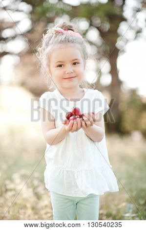 Smiling baby girl 4-5 year old holding strawberry outdoors. Looking at camera. Childhood.
