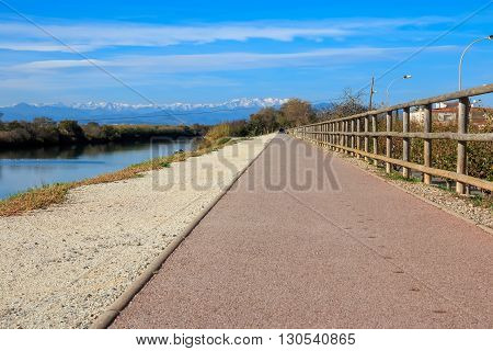 Deserted gravel hiking path among ambient greenery near river with snowy mountains peaks in background