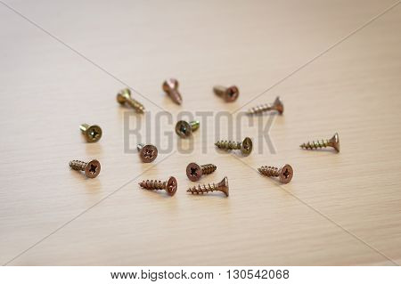 Some drywall Phillips screws on a wooden surface