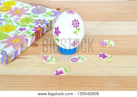 Decoupage Easter egg, napkins with a floral pattern on a natural wooden background