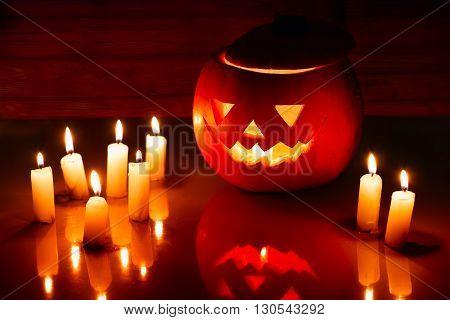 Scary Halloween pumpkin lantern ( jack-o'-lantern) with burning candles on a dark wooden background