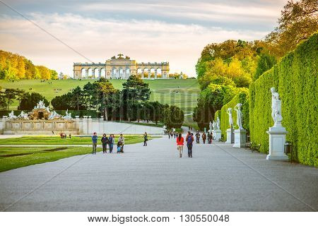 VIENNA, AUSTRIA - CIRCA APRIL 2016: Gloriette building in Schonbrunn gardens with tourist walk on the alley in Vienna. Schonbrunn Palace is one of the most important architectural monuments in Austria