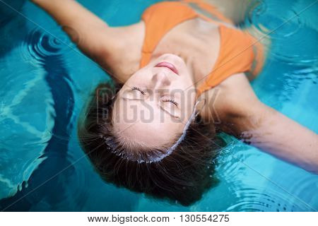 Beautiful female model with body long hairs underwater and wet face skin swimming with pleasure and relaxing in luxury spa pool. Healthy lifestyle woman beauty people health care water treatment