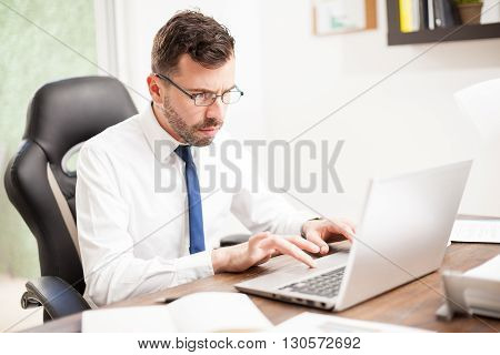 Businessman With Glasses Working On A Laptop