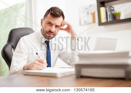 Portrait of an unhappy businessman going to a pile of papers to sign and looking angry and miserable poster
