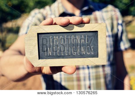 closeup of a young caucasian man showing a label-shaped chalkboard with the text emotional intelligence written in it