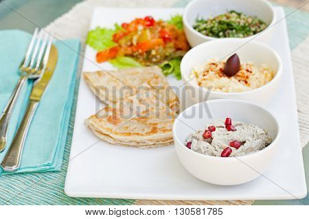 Assortment of dips: hummus, chickpea dip, tabbouleh salad, baba ganoush and flat bread, pita on a plate. Summer outdoor background