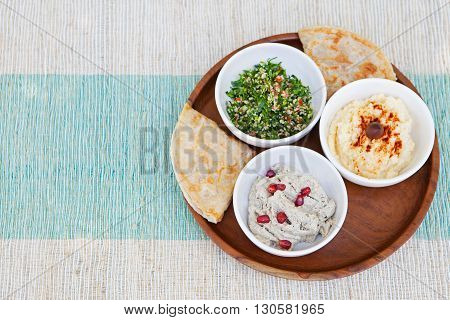 Assortment of dips: hummus, chickpea dip, tabbouleh salad, baba ganoush and flat bread, pita on a plate. Summer outdoor background Copy space